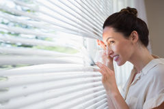 Woman peeking through the blinds Royalty Free Stock Photo