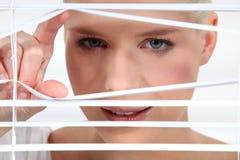 Woman peeking through blinds Stock Photo
