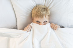 Woman Peeking Through Duvet In Bed Royalty Free Stock Photo
