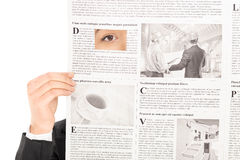 Woman peeking through a hole in newspaper Royalty Free Stock Image