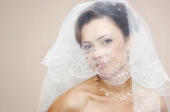Woman peeking out from behind veil Stock Photos