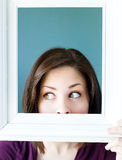 Woman peeking out from a vintage picture frame Royalty Free Stock Photo