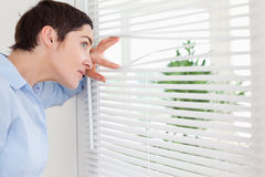 Woman peeking out a window Stock Image