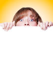 Woman peeking over a blank white placard Royalty Free Stock Photos