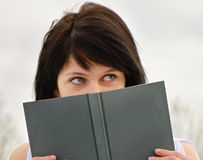 Woman peeking over edge of book Royalty Free Stock Photos