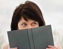 Woman peeking over edge of book Royalty Free Stock Photos