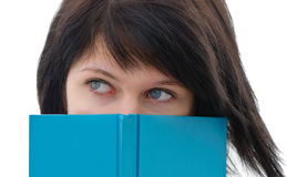 Woman peeking over edge of book Stock Photo