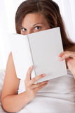 Woman peeking over white book Stock Photos