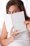 Woman Peeking Over White Book