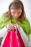 Woman peeking at shopping bags Royalty Free Stock Photography
