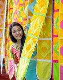 Woman peeks out of the ornamentals curtains Stock Photos
