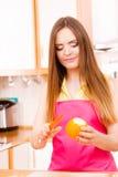 Woman peeled orange fruit with knife Royalty Free Stock Image