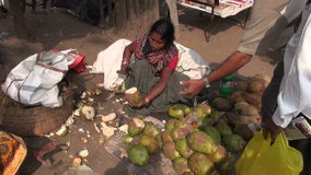 Woman peeling coconut with edge knife of south india stock footage