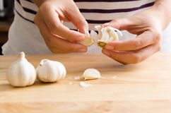 Woman peeling garlic. By hand for cooking stock photos