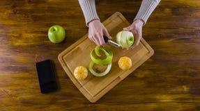 Woman peeling green apple with peeler Stock Image