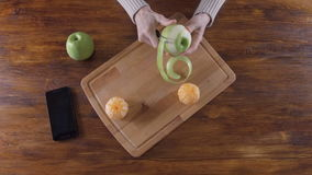 Woman peeling green apple with peeler stock video