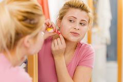Woman peeling off gel mask from face Stock Photo