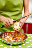 Woman peeling onions Royalty Free Stock Images