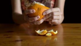 Woman peeling an orange stock video