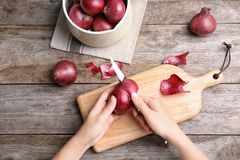 Woman peeling ripe red onion on wooden table. Top view Royalty Free Stock Images