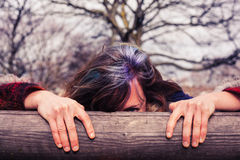 Woman peeping from behind wooden beam Royalty Free Stock Photo