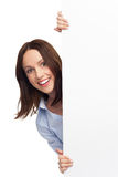 Woman peeping over blank poster Royalty Free Stock Photo