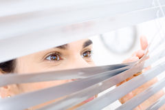 Woman peeping though window Stock Photos