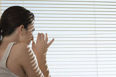 Woman Peering Through Blinds Royalty Free Stock Photography