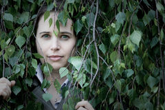 Woman peering through leaves Stock Photo