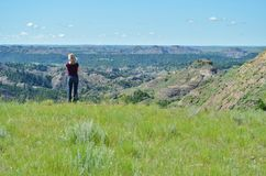 Woman peering out at a valley. Stock Photo