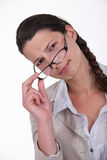 Woman peering over glasses Stock Photo