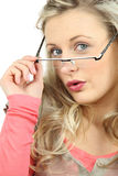 Woman peering over glasses Stock Photo