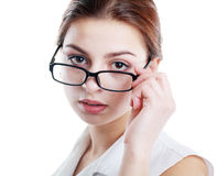 Woman peering over glasses Stock Images