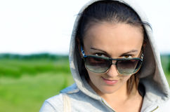 Woman peering over her sunglasses Royalty Free Stock Photography