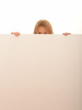 Woman peering over white board Royalty Free Stock Photos