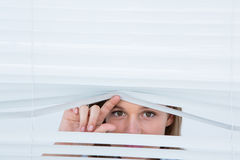 Woman peering through roller blind Stock Image