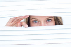 Woman peering through roller blind Royalty Free Stock Images