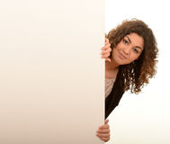 Woman peering round corner Royalty Free Stock Image