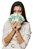 Woman peering at you over a fan of Euro bills Royalty Free Stock Photography