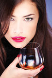 Woman with pelt, holding glass of brandy Royalty Free Stock Images