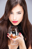 Woman with pelt holding glass of brandy Royalty Free Stock Image