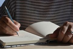 Woman with pen in hand, writing in a journal stock photography