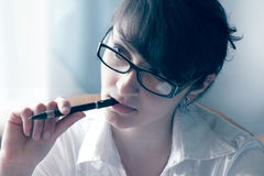 A woman with a pen in his mouth Stock Photography