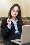 Woman with pen and laptop on sofa Stock Photography