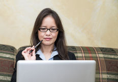 Woman with pen and laptop on sofa Royalty Free Stock Photo