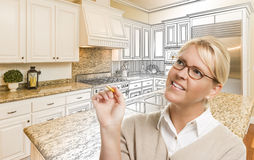 Woman With Pencil Over Custom Kitchen Drawing and Photo Combinat. Creative Woman With Pencil Over Custom Kitchen Design Drawing and Photo Combination Stock Image