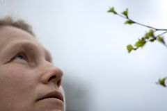 Woman with pensive look. Woman and branch of birch tree with leaves is expanding Stock Images