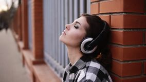 The woman pensively listens to the music in the headphones, leaning on the wall of the fence in the street. My eyes are