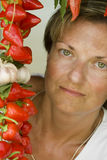Woman and pepper. Colorful portrait of tanned woman with green eyes and red pepper Royalty Free Stock Photos