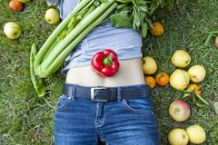 Woman with a pepper on her belly. Over the grass Stock Photo